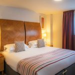 Large-bedroom-with-natural-light-and-comfortable-bed-at-PREMIER-SUITES-Newcastle