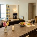 PREMIER-SUITES-Manchester-two-bedroom-kitchen-island-and-living-area